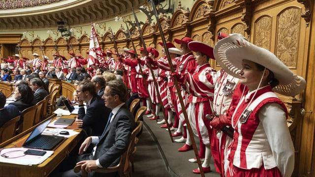 Avertura da la legislatura nova sut protecziun speziala – La truppa «Les Cent-Suisse» da la Fête des Vignerons circumdeschan ils parlamentaris en la sala dal Cussegl naziunal.