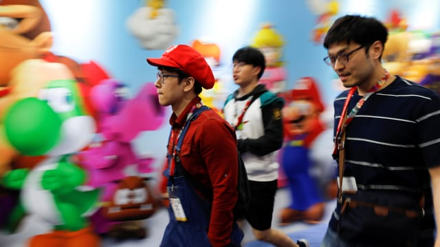 Drei junge Männer – einer davon in einem Super-Mario-Kostüm – laufen an der E3 in Los Angeles vor einem Wandbild mit Figuren aus Nintendo-Spielen.