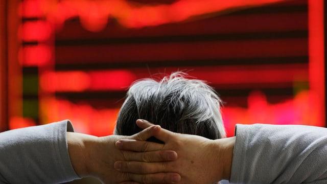 Ein Kopf hinter verschränkten Händen vor roten Börsenkursen.