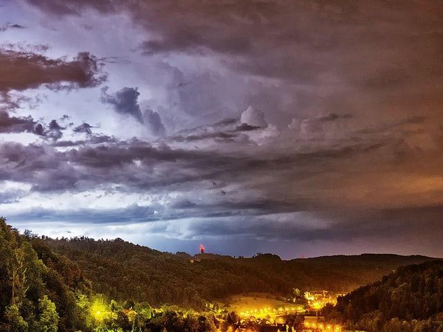 Nächtliche Gewitterstimmung über einer Ortschaft.