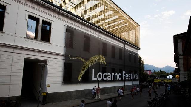 """Grosses Gebäude, an dessen Seite ein Fahne mit der Aufschrift """"Locarno Festival"""" hängt."""