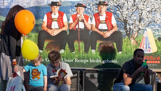 Leute sitzen auf Bank, im Hintergrund Werbung für Appenzeller Käse