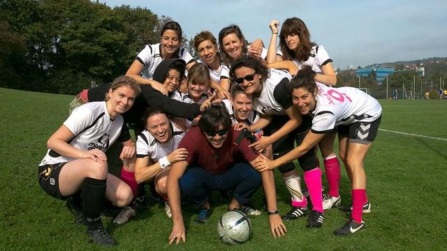 Die Fussballerinnen posieren um einen Mann mit Ball herum.