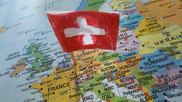 Eine kleine Schweizerfahne steckt auf einer Europakarte in Deutschland