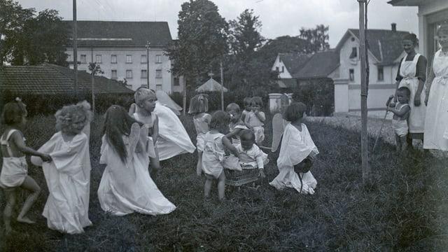 Schwarz-Weiss-Aufnahme aus ca. 1930 mit auf der Wiese spielenden Kindern.