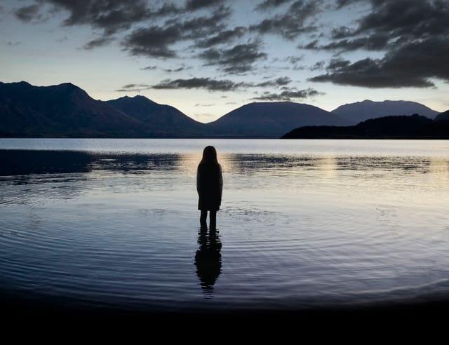 Kind in einem See nach Sonnenuntergang stehend