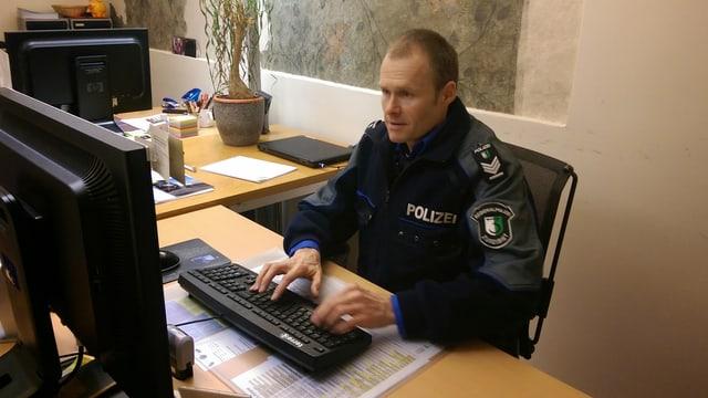 Ein Polizist sitzt vor einem Bildschirm.