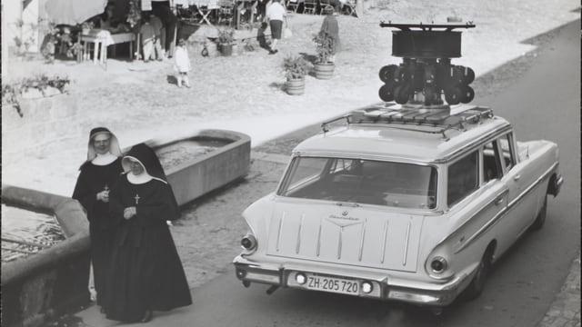 eine schwarz-weiss Aufnahme eines Autos, auf dem etliche Kameras platziert sind