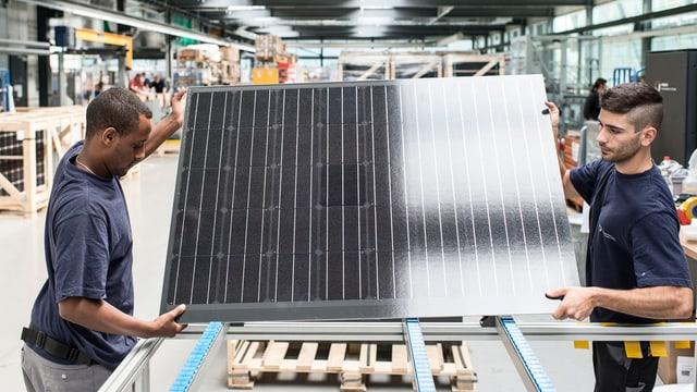 Zwei Männer verpacken ein Solarpanel.