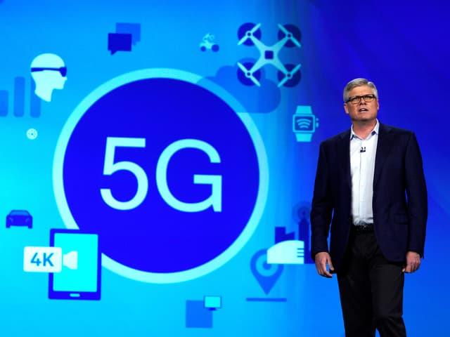 Steve Mollenkopf vor einer Leinwand, darauf schematisch 5G Vernetzung.