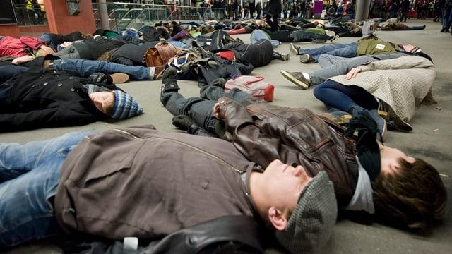 Ein Flashmob im Hauptbahnhof Bern: 50 Personen liegen auf dem Boden.