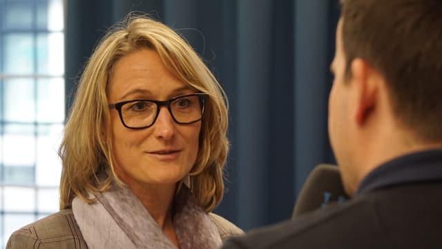 Eine Frau mit Brille wird interviewt.