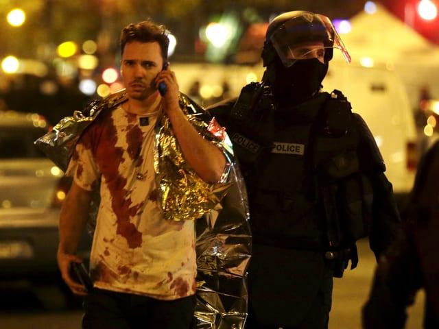 Mann mit blutigem Shirt, daneben ein Polizist.