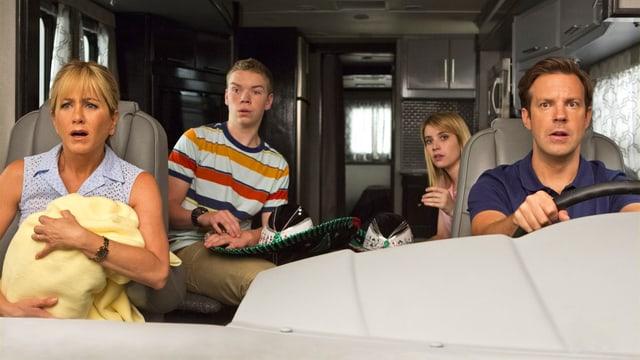 Eine Familie sitzt verschreckt in einem Wohnmobil.