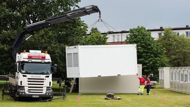 Ein Lastwagen ladet Container ab.