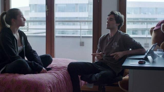 Eine Frau auf dem Bett, ein Mann auf einem Stuhl.
