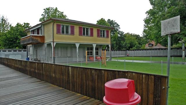 Häuschen, eingezäumter Spielplatz, Holzpritsche des Freibades, Umziehkabinen.