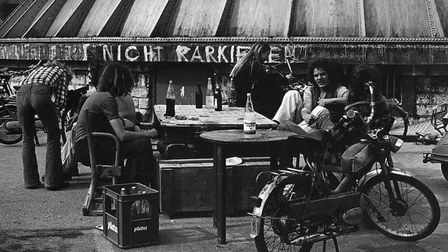 Schwarzweiss-Bild: Leute sitzten vor dem Chessu.