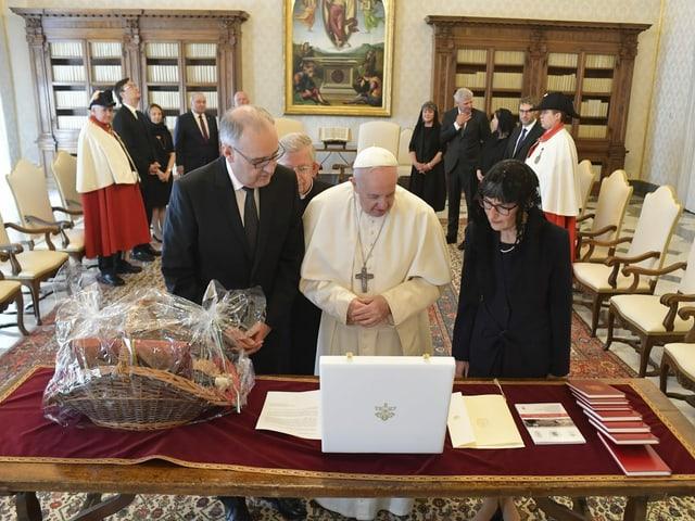 Guy Parmelin und der Papst begutachten Gaben auf einem Tisch.