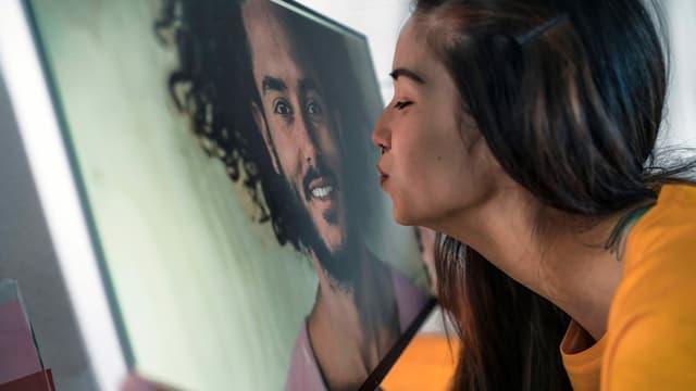 Eine Frau küsst einen Bildschirm, auf dem ein Mann zu erkennen ist.