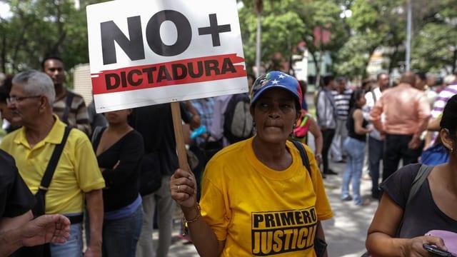 Purtret d'ina demonstranta cun ina tavla cun scrit si «na dictatura» ed in t-shirt cun si «sco emprim giustia»