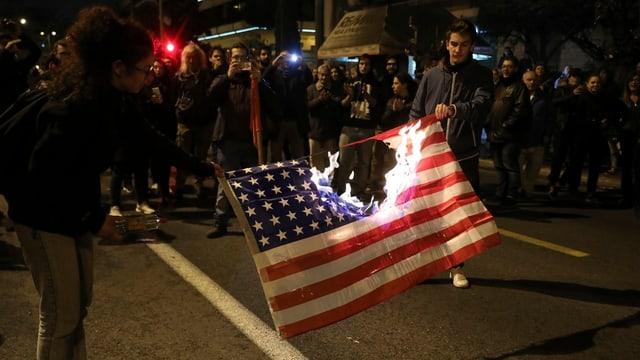 Demonstranten haben eine US-Flagge entzündet