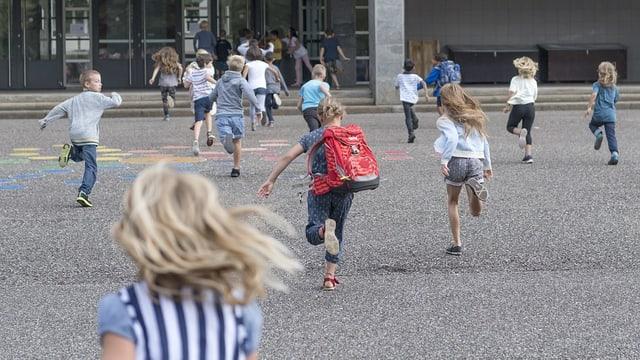 Kinder rennen in die Schule.