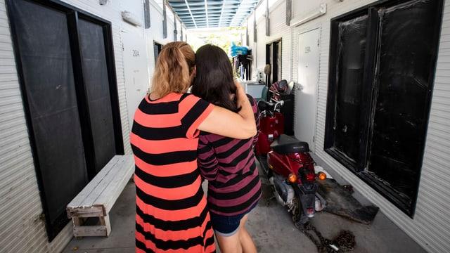 Frau umarmt Mädchen.