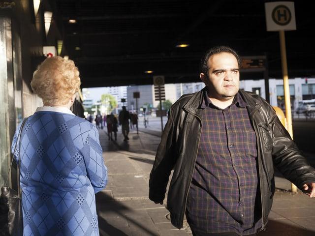 Strassenszene: Ein Mann geht auf dem Bürgersteig an einer älteren Frau vorbei.