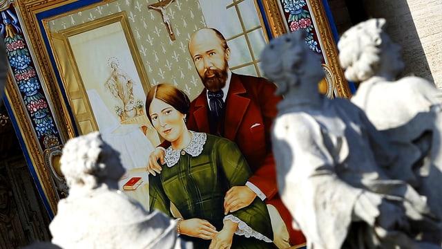 Portrait der Eheleute Louis und Zelie Martin auf einem Wandteppich. der von einem vatikanischen Gebäudebalkon hängt.