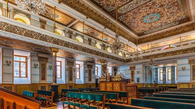 Die Synagoge in Tiflis von innen. Man sieht grüne Bänke. Die Wände sind verziert.