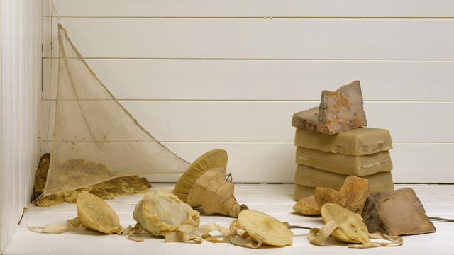 Ein paar Steine und Wachs vor einer weissen Holzwand.