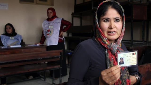 Eine Afghanin präsentiert ihren Wahlrechtsausweis, der in einer Wähler-Anlaufstelle ausgestellt wurde.