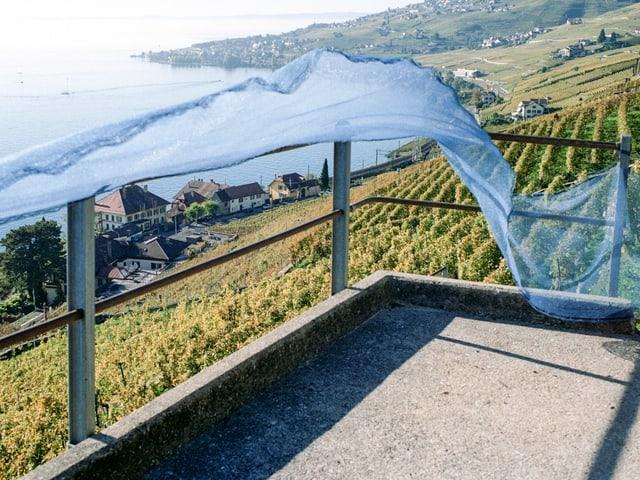 Ein Tuch weht an einem Geländer, von dem aus man über Weinberge und Höfe sieht.