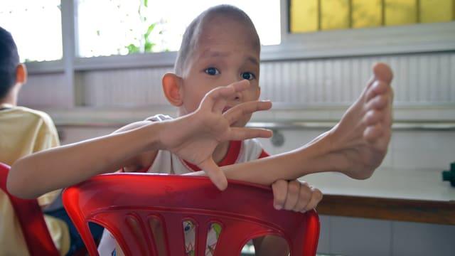 Kind mit dünnen, verbogen-steifen Gliedern, das in einem roten Plastikstuhl sitzt.
