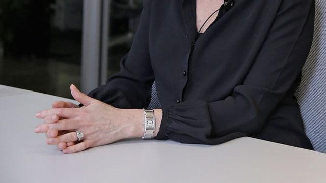Eine Frau sitzt an einem Tisch am Arbeitsplatz.