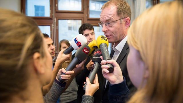 Journalisten mit Mikrofonen umringen Mann mit Brille
