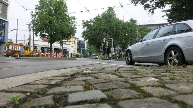 Auto auf einer Strasse, dahinter eine Baustelle