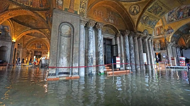 Ein reich verzierter Innenraum einer Kirche steht unter Wasser.