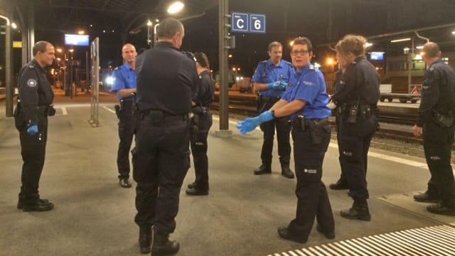 Eine Gruppe Uniformierter nachts auf einem Perron.