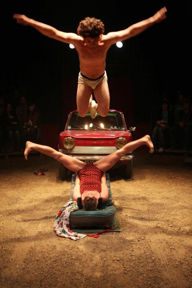 Eien junge Frau in einem rot-schwarzen Badekostüm liegt auf dem Rücken und macht einen Spagat in der Luft. Über ihr springt ein junger Mann in Unterhose mit ausgebreiten Armen. Im Hintergrund ist ein rotes Auto zu sehen.