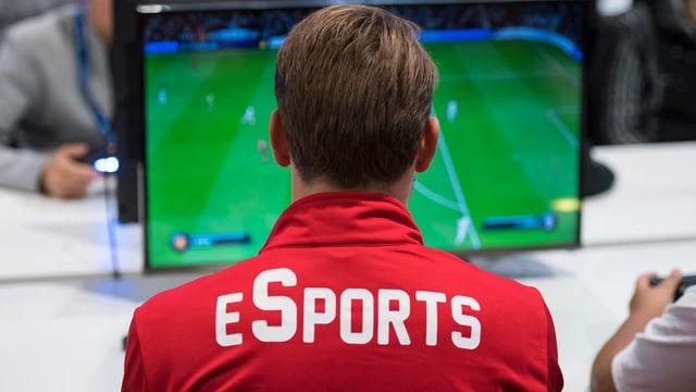 """Ein Mann in einem roten T-Shirt auf dem """"E-Sports"""" geschrieben steht, spielt eine runde Fifa."""