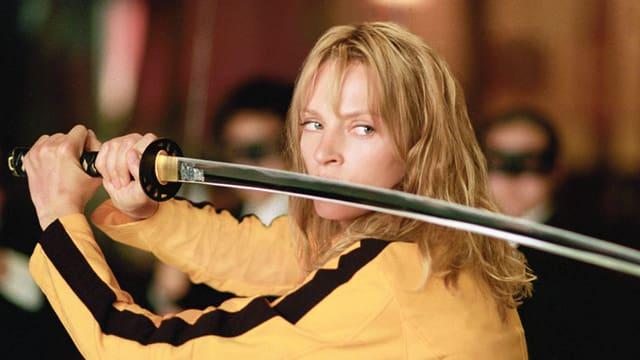 Eine Frau mit gelbem Overall und einem Samuraischwert.