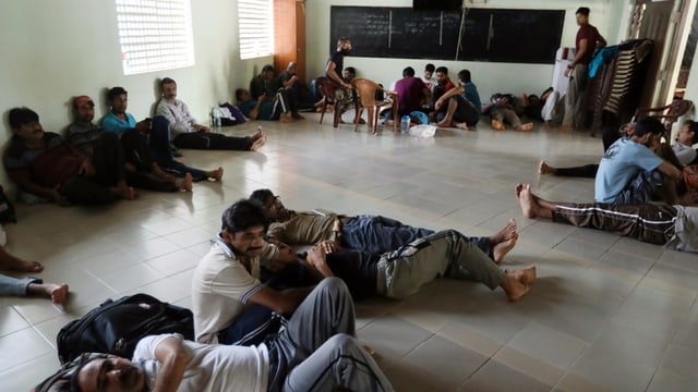 Mànner sitzen und liegen auf einem Boden.