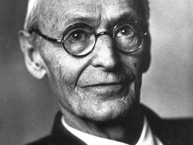 Portrait von Hermann Hesse, der freundlich durch eine Nickelbrille in die Kamera schaut.