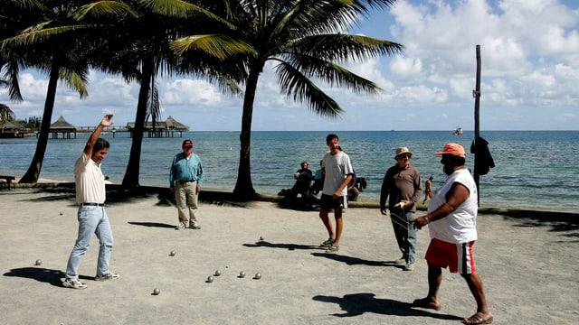 Fünf Männer spielen an einer Strandpromenade Pétanque.