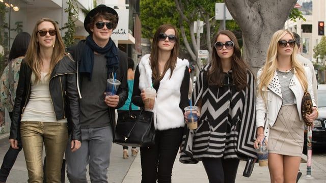 Fünf gut gekleidete Jugendliche mit Sonnenbrillen schlendern durch die Stadt.