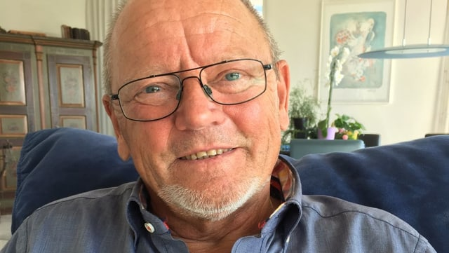 Ein älterer Mann mit Brille und grauem Haar in einem blauen Hemd.