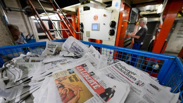 Ein Stapel von Zeitungen, dahinter unscharf Druckmaschinen.