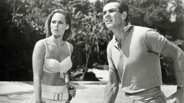 Frau im Bikini und Mann am Sandstrand